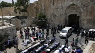 مصلون مسلمون يصلون خارج بوابة الأسباط في القدس القديمة احتجاجا على وضع البوابات الالكترونية عند مداخل الحرم القدسي في 17 يوليو / تموز 2017. (AFP Photo/Ahmad Gharabli)