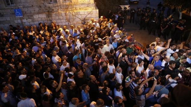 مصلون مسلمون فلسطينيون يتظاهرون أمام باب الأسباط في البلادة القديمة في القدس، 18 يوليو، 2017. (AFP/ AHMAD GHARABLI)