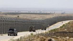 مركبات عسكرية إسرائيلية تسير على الطريق المقابل للسياج الحدوي الذي يفصل الجانبين الإسرائيلي والسوري لهضبة الجولان، 19 يوليو، 2017. (AFP/Menahem Kahana)