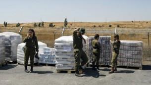 جنود إسرائيليون يقفون بجانب إمدادات غذائية يتم تجهيزها كمساعدات إنسانية للسوريين المتأثرين من الحرب الأهلية في بلادهم، 19 يوليو، 2017. (AFP/Menahem Kahana)