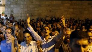 مصلون مسلمون فلسطينيون يصلون أمام باب الأسباط، المدخل الرئيسي إلى المسجد الأقصى في الحرم القدسي في البلدة القديمة لمدينة القدس، 20 يوليو، 2017. (AFP PHOTO / AHMAD GHARABLI)