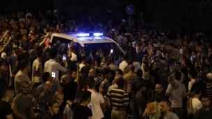 متظاهرون فلسطينيون يحاولون سد طريق أمام مركبات الشرطة الإسرائيلية خارج بابا الأسباط، المدخل الرئيسي إلى المسجد الأقصى في الحرم القدسي في البلدة القديمة لمدينة القدس، 22 يوليو، 2017. (AFP PHOTO / AHMAD GHARABLI)