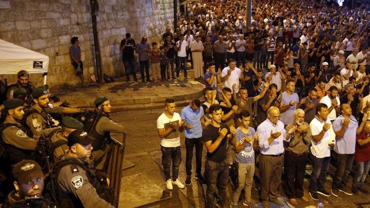 مصلون مسلمون فلسطينيون يصلون أمام باب الأسباط، المدخل الرئيسي إلى المسجد الأقصى في الحرم القدسي في البلدة القديمة لمدينة القدس، 24 يوليو، 2017. (AFP PHOTO / AHMAD GHARABLI)