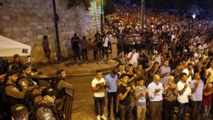 قوات الأمن الإسرائيلية تقف إلى جانب المصلين المسلمين الفلسطينيين خارج بوابة الأسباط، وهي نقطة وصول رئيسية إلى الحرم القدسي في البلدة القديمة في القدس، 24 يوليو / تموز 2017. (AFP/Ahmad GHARABLI)