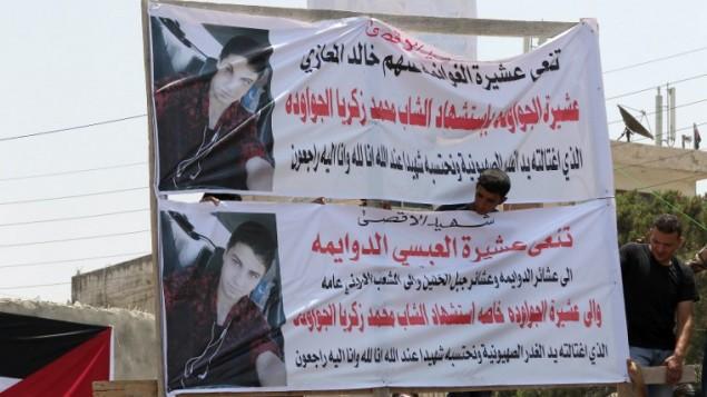 لافتات تحمل صورة محمد جواودة (17 عاما)، الذي قُتل في نهاية الأسبوع عندما قام بمهاجمة حارس أمن في مقر السفارة الإسرئيلية في العاصمة الأردنية بمفك براغي، خلال جنازته في عمان، 25 يوليو، 2017. (Khalil Mazraawi/AFP)
