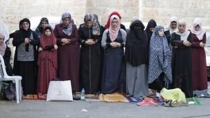 نساء مسلمات يأدين الصلاة خارج البلدة القديمة لمدينة القدس، 25 يوليو، 2017. (AFP Photo/Ahmad Gharabli)