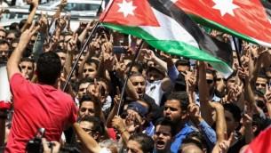 يحتج المتظاهرون الأردنيون خلال مظاهرة بالقرب من السفارة الإسرائيلية في العاصمة عمان في 28 يوليو / تموز 2017، رافعين الأعلام الوطنية ويهتفون بالشعارات, مطالبون بإغلاق السفارة وطرد السفيرة وإلغاء معاهدة السلام عام 1994 مع إسرائيل. (AFP PHOTO / KHALIL MAZRAAWI)