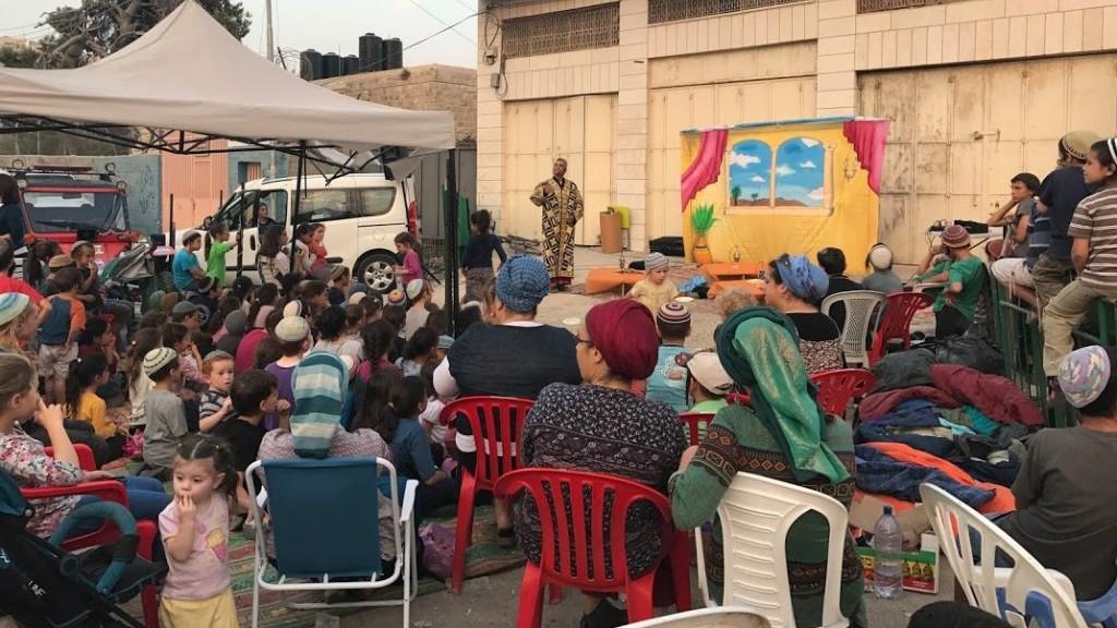 اطفال مستوطنين في منزل استولى عليه مستوطنين في الخليل يشاهدون مسرحية خارج المبنى، 26 يوليو 2017 (Jacob Magid)