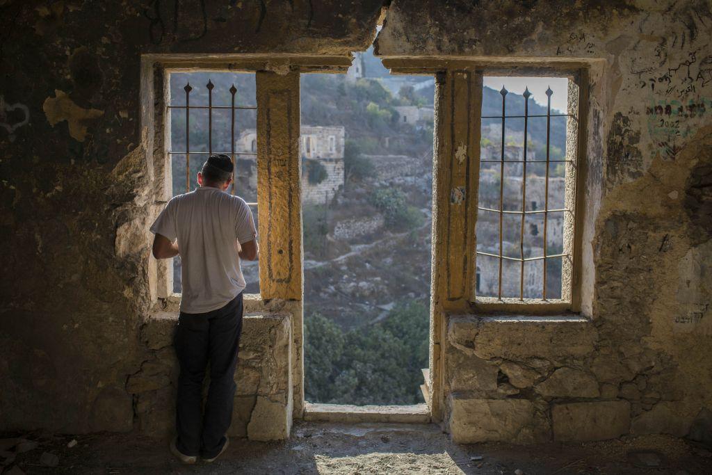 """يهودي أرثوذكسي يقرأ صلاة تشليخ في مبنى في لفتا، عند مدخل القدس، بالقرب من نبع لفتا. تشليخ (""""إلْقاء"""") هي ممارسة التي تجري في رأس السنة اليهودية الجديدة، عندما يكون من العادة رمي قطعة من الخبز في جسم طبيعي من المياه المتدفقة م أجل """"إلْقاء"""" خطايا العام الماضي بعيدا. (Yonatan Sindel/Flash90)"""