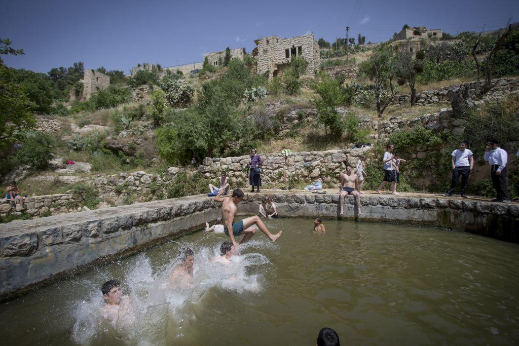 إسرائيليون يستجمون في نبع لفتا في القدس في 26 أبريل 2016، حيث بلغت درجات الحرارة 40 درجة في بعض أنحاء البلاد. (Photo by Yonatan Sindel/Flash90)