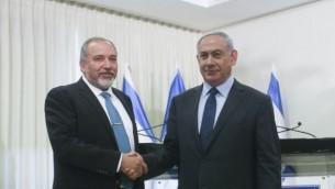 رئيس الوزراء بنيامين نتنياهو (يمين) وزعيم حزب يسرائيل بيتينو أفيغدور ليبرمان يتصافحان بعد توقيع اتفاق الائتلاف في الكنيست يوم الأربعاء 25 مايو 2016. (Yonatan Sindel/Flash90)