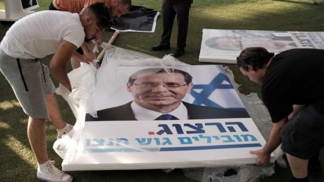 عمال يحملون لافتات دعاية انتخابية كبيرة خلال تجمع لدعم رئيس حزب 'العمل' يتسحاق هرتسوغ في تل أبيب، 26 يونيو، 2017. (Tomer Neuberg/Flash90)