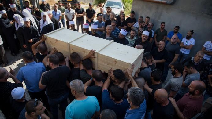 اقرباء واصدقاء يحملون نعش الشرطي الدرزي الإسرائيلي هايل ستاوي، خلال تشييع جثمانه في قرية المغار في شمال البلاد، 14 يوليو 2017 (Basel Awidat/Flash90)