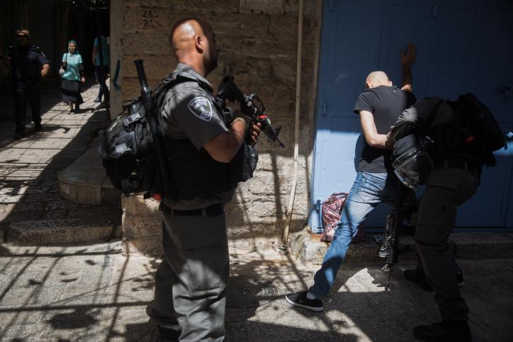 أفراد من شرطة حرسة الحدود يقومون بتفتيش جسدي لشاب فلسطيني في البلدة القديمة في القدس بعد الهجوم الذي وقع بالقرب من الحرم القدس، الذي قام خلاله ثلاثة مواطنين إسرائيليين عرب بقتل شرطيين إسرائيليين بعد إطلاق التار عليهما. 14 يوليو، 2017. (Hadas Parush/FLASH90)
