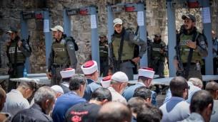 يقود مسؤولو الوقف صلاة المسلمين خارج الحرم القدسي في البلدة القديمة في القدس في 16 يوليو / تموز، مع البوابات الاكترونية في الخلفية. (Yonatan Sindel/Flash90)
