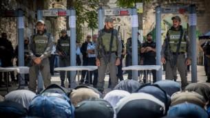 المسلمون يصلون أمام البوابات الالكترونية التي وضعت خارج الحرم القدسي، في المدينة القديمة في القدس، 16 يوليو 2017. (Yonatan Sindel/Flash90)
