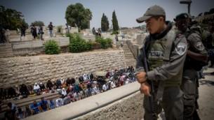 مصلون مسلمون يؤدون صلاة الظهر جانب بوابة الأسباط، خارج الحرم القدسي، في البلدة القديمة في القدس، 20 يوليو 2017. (Miriam Alster/Flash90)