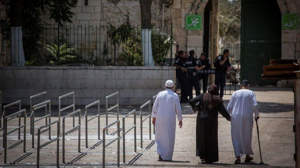 عناصر الشرطة يحرسون احد مداخل الحرم القدسي، بينما يمشي مجموعة مسلمين بجانب حواجز حديدية تم وضعها في الموقع بعد هجوم وقع هناك، 25 يوليو 2017 (Hadas Parush/Flash90)