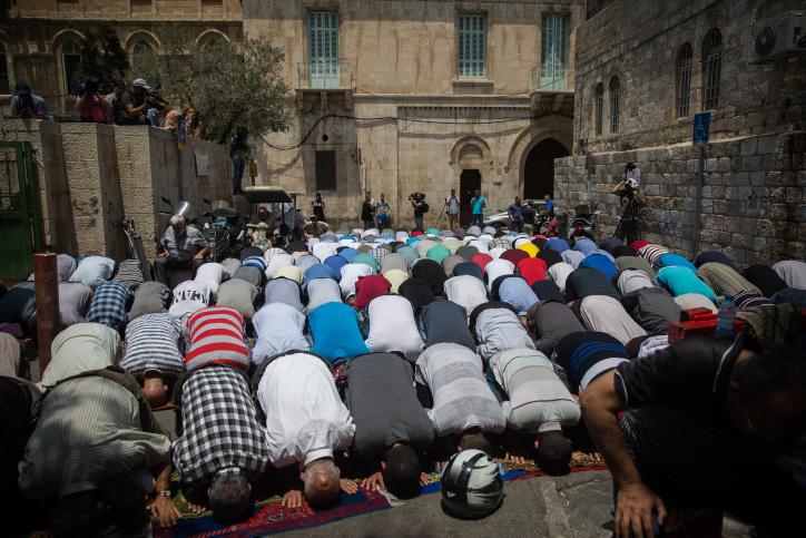 مصلون مسلمون يصلون عند مدخل الحرم القدسي عند باب الأسباط في القدس القديمة، 25 يوليو، 2017. (Hadas Parush/Flash90)