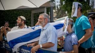 ويحمل نشطاء الجناح اليميني مايكل بن آري (وسط) وإيتامار بن جفير (يسار) يحملان تابوتا مزيفا مغطى بأعلام إسرائيلية أثناء احتجاج على إزالة البوابات الالكترونية وغيرها من التدابير الأمنية في الحرم القدسي، بالقرب من مقر رئيس الوزراء في القدس ، 27 يوليو 2017. (Yonatan Sindel/Flash90)