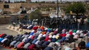 مصلون مسلمون يصلون امام عناصر الشرطة الإسرائيلية في حي راس العامود في القدس الشرقية، 28 يوليو، 2017. (Hadas Parush/Flash90)