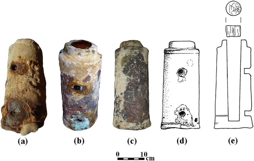 حجرة معالجة بارود برونزية رق م1: (A) كما كانت عند استخراجها؛ (b) حجرة معالجة البارود بعد إزالة طبقة التحجير، مع ثقبين حيث المقبض الحديدي مفقود؛ (c) حجرة معالجة البارود بعد إزالة طبقة التحجير، بعيدا عن المقبض المفقود؛ (d) رسم لحجرة معالجة البارود رقم 1، حيث المقبض المفقود؛ و(e) مقطع عرضي لحجرة معالجة البارود وحشوتها الخشبية (الحشوة الخشبية 1). (Drawing: R. Pollak, Photos: E. Galili)