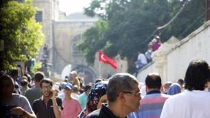 مصلين مسلمين عند بوابة الأسباط الذين رفضوا دخول الحرم القدسي في 27 يوليو 2017، حتى بعد أن بدأ الآلاف في الوصول الى الموقع المقدس. واحد المتظاهرين يحمل العلم التركي. (Dov Lieber / Times of Israel)