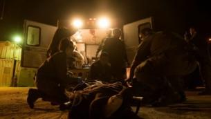 في هذه الصورة غير المؤرخة المقدمة في 19 يوليو، 2017، جنود من الجيش الإسرائيلي يقدمون العلاج لسوري مصاب في منطقة هضبة الجولان. (IDF spokesperson)