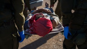 في هذه الصورة غير المؤرخة المقدمة في 19 يوليو، 2017، جنود من الجيش الإسرائيلي يقومون بإخلاء سوري مصاب في منطقة هضبة الجولان. (IDF spokesperson)