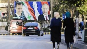 سوريون يمرون من أمام صورة عملاقة للرئيس السوري بشار الأسد (من اليسار) ونظيره الروسي فلاديمير بوتين (من اليمين) في مدينة حلب شمال سوريا، 9 مارس، 2017. (AFP Photo/Joseph Eid/ File)
