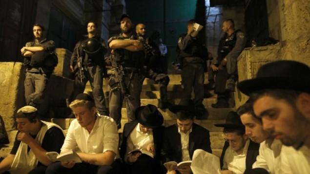 حرس الحدود يحرسون بينما يصلي رجال يهود عند احد بوابات القدس القديمة في ذكرى دمار الهيكلين، 31 يوليو 2017 (AFP Photo/Menahem Kahana)