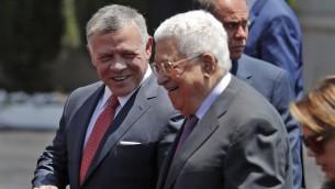 الملك عبد الله الثاني، من يسار الصورة، يتحدث مع رئيس السلطة الفلسسطينية محمود عباس بعد وصوله إلى مدينة رام الله في الضفة الغربية، 7 أغسطس، 2017. (AFP/Ahmad GHARABLI)