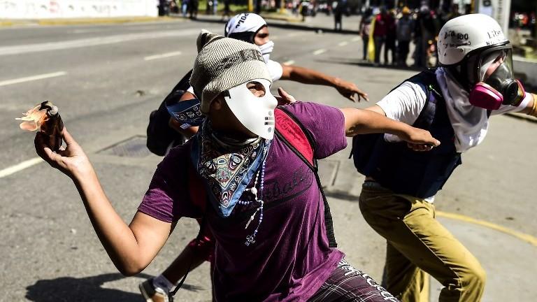 ناشط من المعارضة يلقي بزجاجة حارقة خلال اشتباكات مع فوى الأمن في العاصمة الفنزويلية كاراكس، 12 أغسطس، 2017. (AFP Photo/Ronaldo Schemidt)