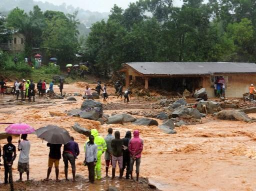 ينظر المارة إلى الأمطار التي أغرقت المباني المتضررة في منطقة من فريتاون في 14 أغسطس / آب 2017، بعد أن هزت الانهيارات الأرضية عاصمة ولاية سيراليون في غرب أفريقيا. (SAIDU BAH / AFP)