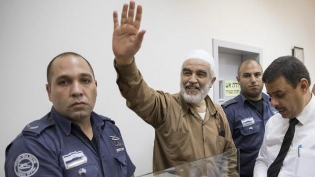 الشيخ رائد صلاح، في وسط الصورة، خلال وصوله إلى محكمة الصلح في ريشون لتسيون، 15 أغسطس، 2017. (AFP/JACK GUEZ)
