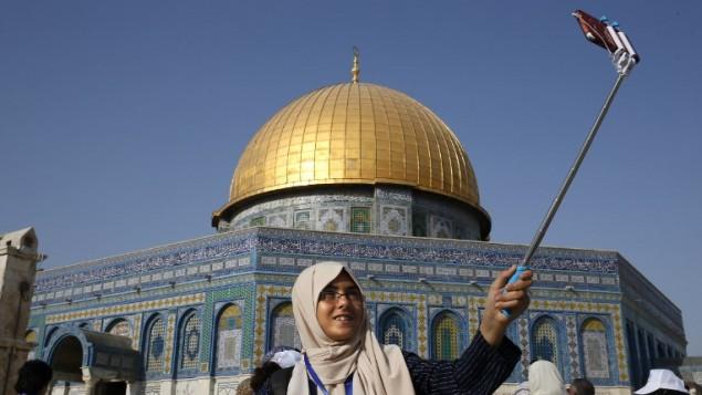 طفلة فلسطينية من قطاع غزة تلتقط صورة 'سيلفي' من أمام قبة الصخرة في مجمع المسجد الأقصى في البلدة القديمة في مدينة القدس، 20 أغسطس، 2017، خلال زيارة تقوم بها إلى لمدينة للمرة الأولى في حياتها في إطار برنامج تبادل تنظمه وكالة الأمم المتحدة لغوث وتشغيل اللاجئين الفلسطينيين. (AFP PHOTO / AHMAD GHARABLI)