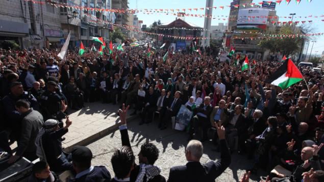 فلسطينيون يلوحون بأعلام فلسطينية خلال تظاهرة في مدينة رام الله في الضفة الغربية، الخميس، 29 نوفمبر. (Issam Rimawi/Flash90)