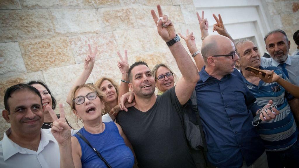 ميني نفتالي (وسط الصورة)، المدير السابق لمنزل رئيس الوزراء، والناشط الإسرائيلي إلداد يانيف (الثاني من اليمين) خارج قاعة المحكمة العليا في القدس، 24 أغسطس، 2017.(Yonatan Sindel/Flash90)