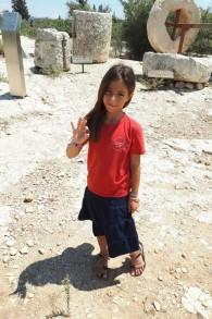 هاليل هليفي (8 أعوام) بالقرب من الموقع الأثري الذي عثرت فيه على عملة نقدية قديمة بقيمة نصف شيكل، في صورة لها تم التقاطها في أغسطس 2017. (courtesy)