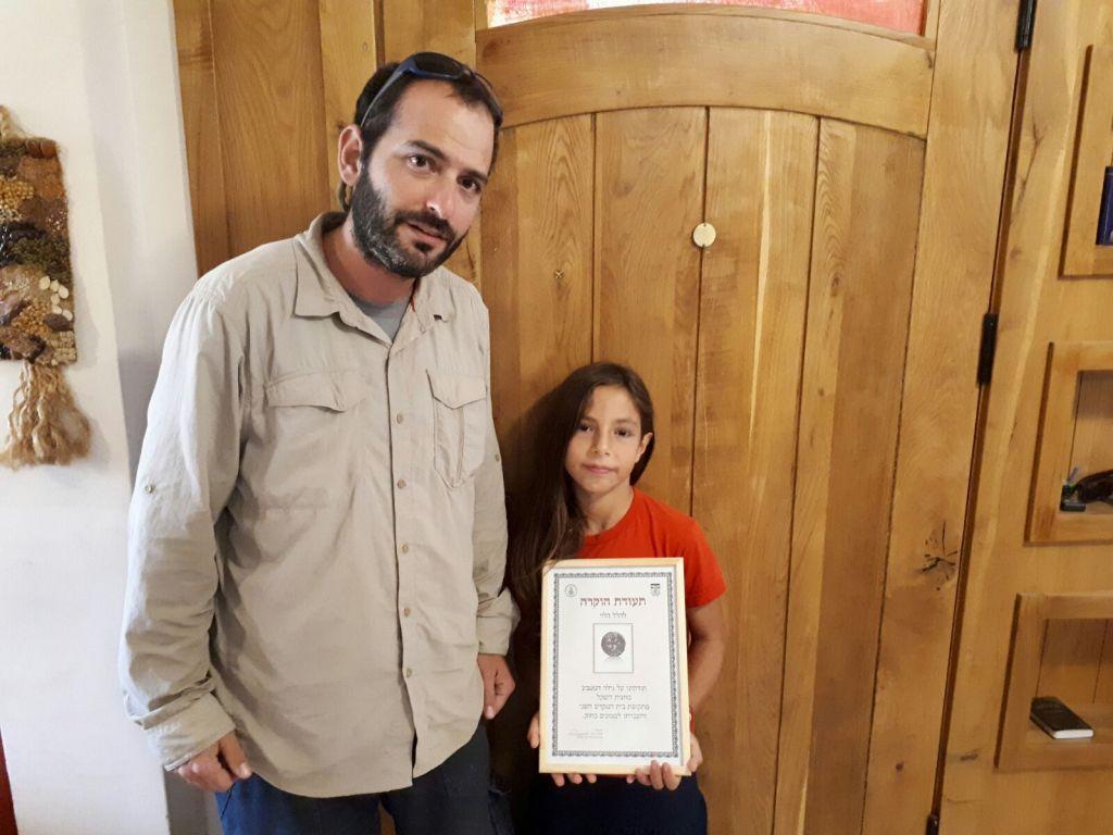 هاليل هليفي (8 أعوام) مع عالم آثار من الإدارة المدنية الذي استلم عملة معدنية يعود تاريخها إلى 2,000 عام منها في منزلها في نيفيه تسوف، 23 أغسطس، 2017. (courtesy)