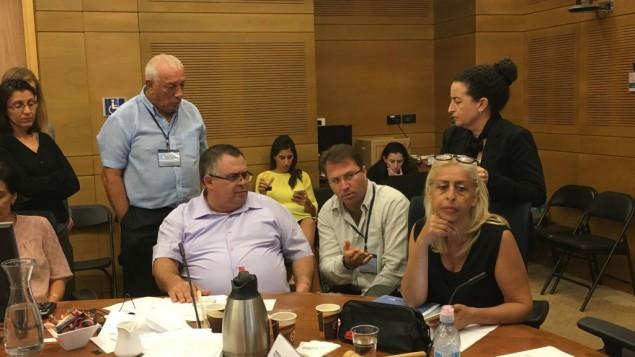 عضو الكنيست دافيد بيتان، يجلس إلى جانب موشيه أفراهامي، المدير المالي لشركة SpotOption، ومديرة لجنة الإصلاح، أريئيلا مالكا، في جلسة لللجنة لمناقشة حظر صناعة الخيارات الثنائية، 7 أغسطس، 2017. (Times of Israel)