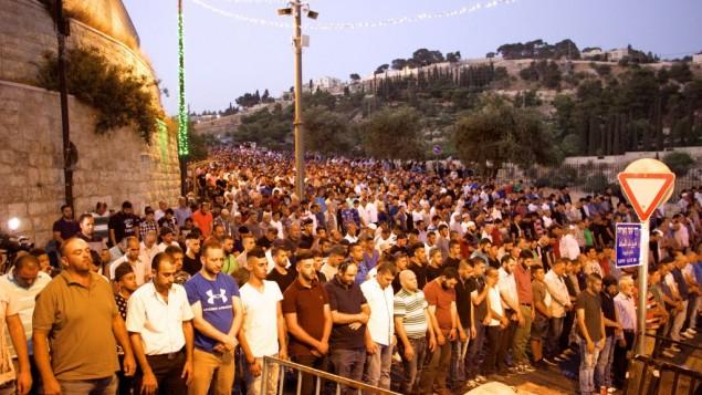 آلاف المصلين المسلمين يشاركون في صلاة المساء من أمام باب الأسباط في البلدة القديمة في القدس، رافضين دخول الحرم القدسي، 25 يوليو، 2017. (Dov Lieber /Times of Israel)