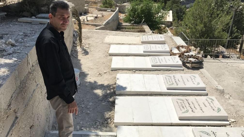 يقف حسن دبش بجانب قبور زوجته السابقة وخمسة أطفاله الذين قتلوا في حادث طرق في الضفة الغربية في 27 يونيو / حزيران 2017. (Jacob Magid/Times of Israel)