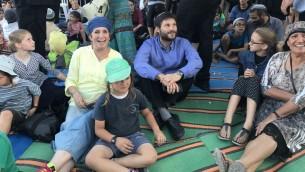 عضو البيت اليهودي بيتساليل سموتريتش (القميص الأزرق) يجلس بين المئات الذين تجمعوا للاحتجاج في مستوطنة سانور التي تم إخلاؤها في شمال الضفة الغربية. (Jacob Magid/The Times of Israel)