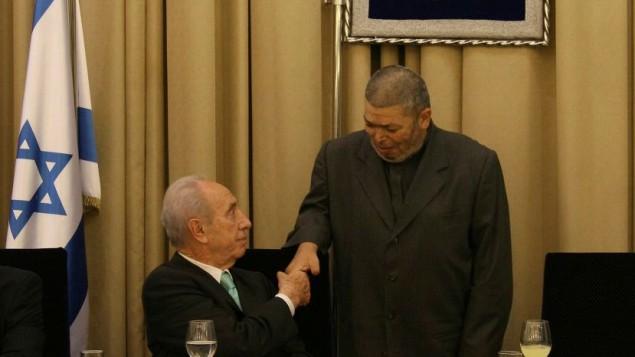 رئيس الدولة شمعون بيرس يصافح الشيخ عبد الله نمر درويش (من اليمين) خلال وجبة إفطار في مقر إقامة رئيس الدولة في القدس، 9 سبتمبر، 2008. (Anna Kaplan/Flash90)