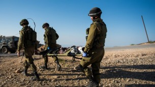 في هذه الصورة غير المؤرخة التي تم نشرها في 19 يوليو، 2017، يقوم جنود إسرائيليون بنقل مصاب سوري في منطقة هضبة الجولان. (الجيش الإسرائيلي)