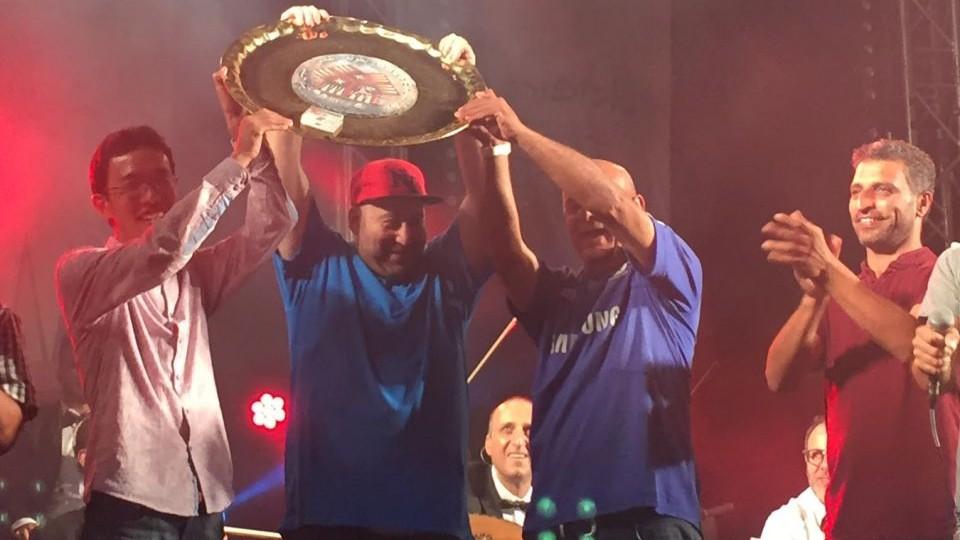 بطل بطولة الشيش بيش في القدس غادي كارميلي (يمين) يحمل على الكأس، إلى جانب اللاعب العالمي فلافل (وسط) والبطل العالمي السابق موشيزوكي في 24 أغسطس. (Times of Israel staff)