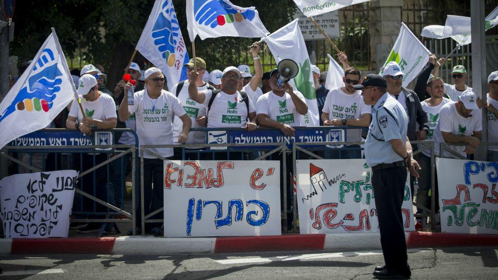 عمال يحملون لافتات اثناء التظاهر امام منزل رئيس الوزراء في القدس ضد اغلاق خزان الامونيا في مدينة حيفا الشمالية، 29 مارس 2017 (Yonatan Sindel/Flash90)