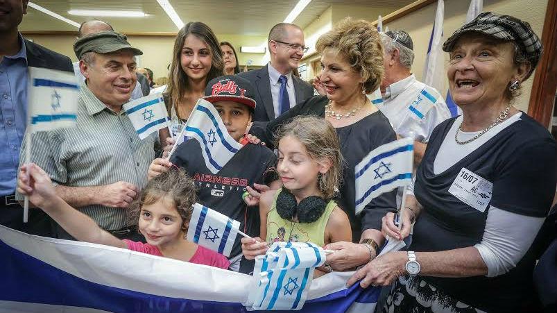 رئيس الوكالة اليهودية، ناتان شارانسكي، ووزير الهجرة والاستيعاب السابقة صوفا لاندفر، مع عائلة من فرنسا هاجرت إلى إسرائيل في يوليو 2014. (David Salem)