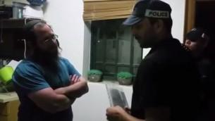 إلكانا بيكار (من اليسار) يتحدث مع شرطي إسرائيلي من شرطة يهودا والسامرة الذي يقوم بتسليمه أمر إبعاد عن الضفة الغربية في منزله في مستوطنة يتسهار، 16 مايو، 2017. (Screen capture/YouTube)